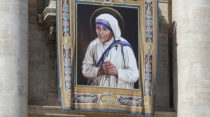 FILE - In this Thursday, Sept. 1, 2016 file photo, a tapestry showing Mother Teresa hangs from the central balcony of St. Peter's Basilica, in St. Peter's Square, at the Vatican. For many of the poor and destitute whom Mother Teresa served, the tiny nun was a living saint. Many at the Vatican would agree, but the Catholic Church nevertheless has a grueling process to make it official, involving volumes of historical research, the hunt for miracles and teams of experts to weigh the evidence. (AP Photo/Alessandra Tarantino, File)